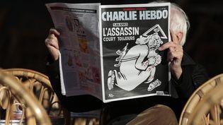 """Un homme lit """"Charlie Hebdo"""" à la terrasse d'un café, le 6 janvier 2016, à Nice (Alpes-Maritimes). (ERIC GAILLARD / REUTERS)"""