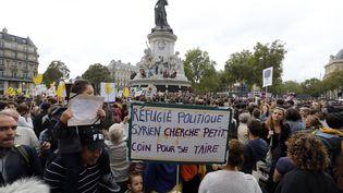 Une personne tient une pancarte au rassemblement en soutien aux migrants organisé à Paris le 5 septembre 2015. (FRANCOIS GUILLOT / AFP)