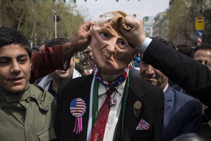 Des Iraniens manifestent autour d'un masque du président américain Donald Trump, le 12 avril 2019 à Téhéran (Iran), après l'inscription par l'administration américaine des Gardiens de la révolution sur la liste des organisations terroristes. (ROUZBEH FOULADI / NURPHOTO / AFP)