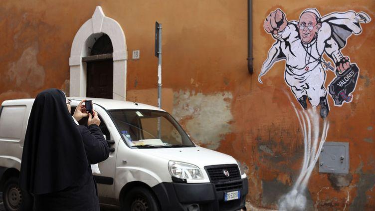 Une religieuse prend en photo un graffiti représentant le pape François en superhéros sur un mur de Rome (Italie), le 29 janvier 2014. (ALESSANDRO BIANCHI / REUTERS)