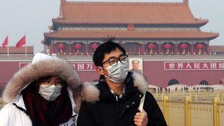 Deux touristes portent un masque de protection sur la placeTian'anmen, à Pékin (Chine), le 28 janvier 2020. (KOKI KATAOKA / YOMIURI / AFP)
