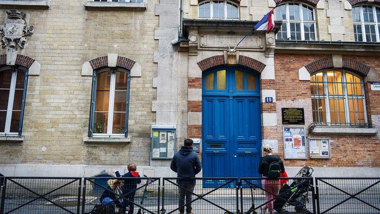 Des parents devant l'école Blomet, à Paris, où un enfant a été testé positif au coronavirus en mars 2020. (ISA HARSIN/SIPA)