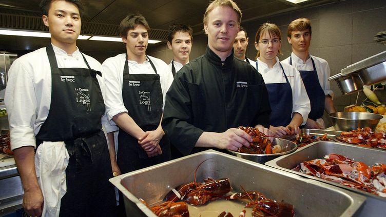 Le chef étoiléNicolas Le Bec (au c.) entouré de son équipe dans l'un de ses anciens restaurants, La Cour des loges,le 14 février 2002 à Lyon (Rhône). (JEAN-PHILIPPE KSIAZEK / AFP)