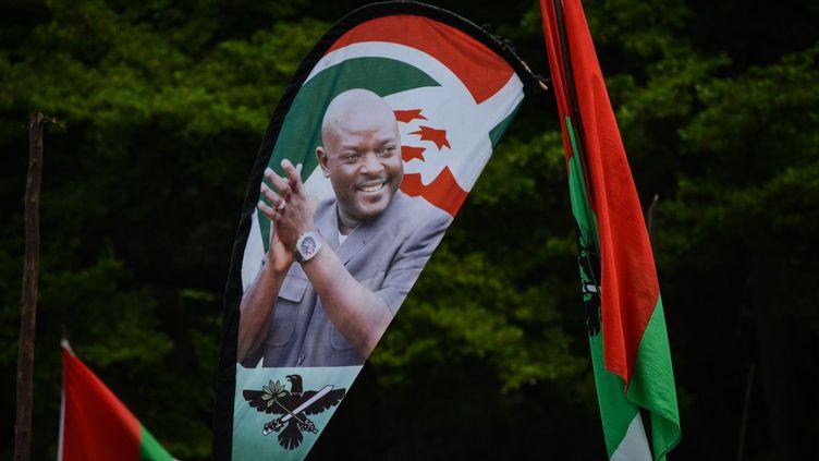 Un portrait du président burundais Pierre Nkurunziza, décédé le 8 juin 2020,imprimésur un drapeau lors d'un meeting du parti au pouvoir, organisé le 14 mai 2018 dans le cadre du référendum constitutionnel controversé prévu trois jours plus tard. (STRINGER / AFP)