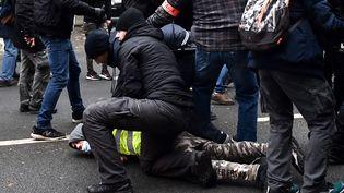 """Des policiers appliquant la technique du plaquage ventral pendant une manifestation des """"gilets jaunes"""", le 29 décembre 2018. (illustration) (FRANCOIS LO PRESTI / AFP)"""
