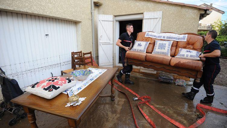Des pompiers aident des habitants d'Alès (Gard) à nettoyer leurs maisons après des inondations, le 20 septembre 2014. (SYLVAIN THOMAS / AFP)