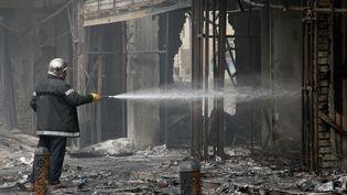 Un pompier éteind un incendie à Bagdad, sur les ruines des lieux d'un attentat, le 3 juillet 2016. (AMIR SAADI / ANADOLU AGENCY / AFP)