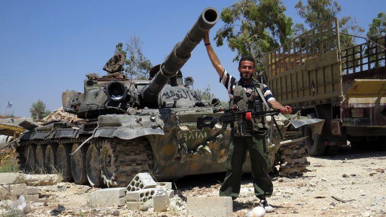 Un rebelle syrien pose devant un tank le 14 juin 2013 à Sarmin en Syrie. (MOHAMED KADDOUR / SHAAM NEWS NETWORK)