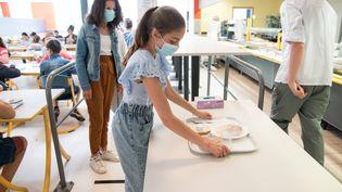 Une élève récupère un plateau repas dans le restaurant scolaire de son collège, le 2 juin 2020, à Beaucamps-Ligny (Nord). (JULIE SEBADELHA / AFP)