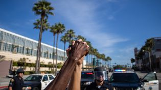 Deux manifestants se tiennennt la main devant un cordon de police le 31 mai 2020 à Long Beach (Etats-Unis), lors d'une manifestation contre les violences policières. (APU GOMES / AFP)
