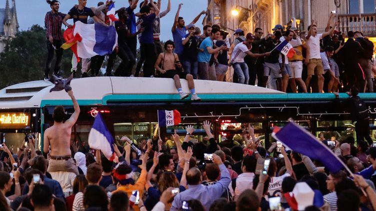 Des supporters français massés sur un bus fêtent la victoire en demi-finale de la Coupe du monde, le 10 juillet 2018, dans le centre de Paris. (THOMAS SAMSON / AFP)