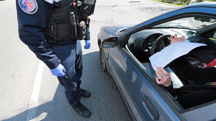 Un gendarme contrôle les attestations de déplacements des automobilistes, à Quimperlé (Finistère), le 26 mars 2020. (FRANCOIS DESTOC / MAXPPP)