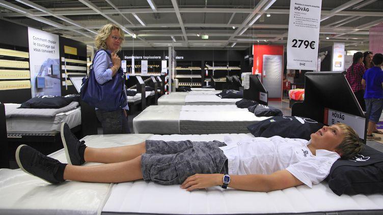 Un jeune homme teste un lit dans un magasin Ikea français, en septembre 2013, sans aucune intention manifeste de se cacher. (PHILIPPE TURPIN / PHOTONONSTOP / AFP)