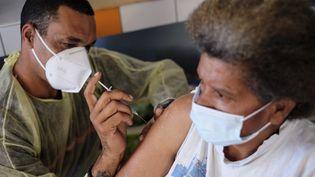 Un pompier administre une dose de vaccin à une membre de la tribu Kouma, le 11 octobre 2021 près de La Foa (Nouvelle-Calédonie). (THEO ROUBY / AFP)