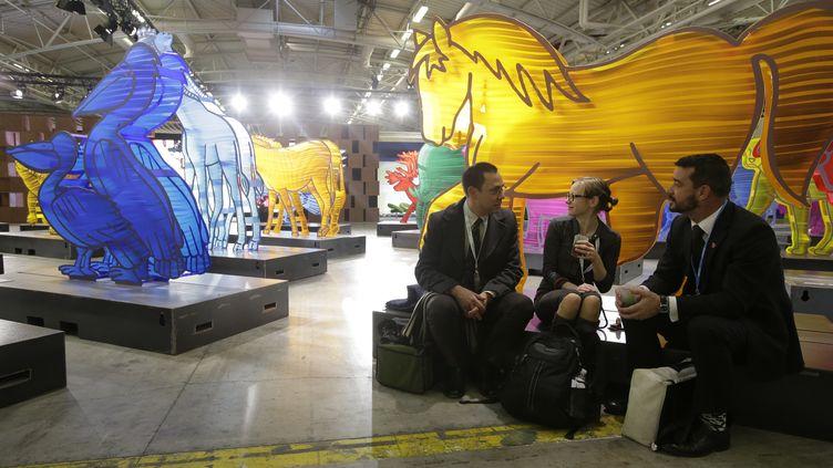 Des membres des délégations prennent une pause pendant la conférence climat (COP21), le 30 novembre 2015 au Bourget. (JACKY NAEGELEN / REUTERS)