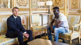 Emmanuel Macron et Mamadou Gassama, le sans-papiers qui a sauvé un enfant suspendu dans le vide à Paris, le 28 mai 2018 à l'Elysée. (JACQUES WITT / SIPA)