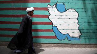 Un homme passe devant une peinture murale sur le mur de l'ancienne ambassade américaine à Téhéran, Iran, le 9 mai 2018. (FATEMEH BAHRAMI / ANADOLU AGENCY)