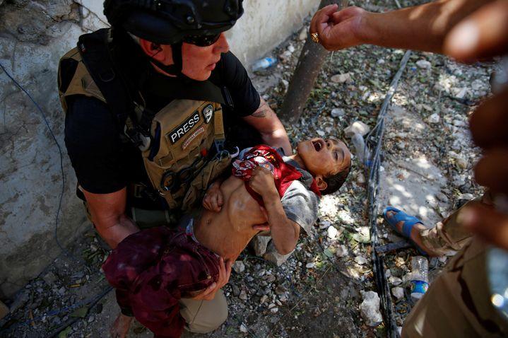 Des militaires versent de l'eau sur la tête d'un enfant déshydraté et amaigri après l'avoir secouru, dans la vieille ville de Mossoul (Irak), le 13 juin 2017. (ERIK DE CASTRO / REUTERS)