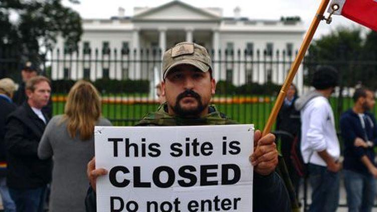 Un manifestant protestant le 13-10-2013 devant la Maison blanche contre le shutdown (fermeture) des administrations fédérales, imposée par l'impossibilité d'un accord budgétaire au Congrès des Etats-Unis entre républicains et démocrates. (AFP - Jewel Samad)