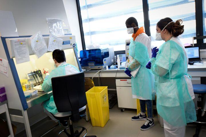 Du personnel médical testeun échantilon prélevé chez un patient potentiellement atteint de Covid-19, le 26 février 2020 dans un laboratoire de l'IHU de Marseille. (GERARD JULIEN / AFP)