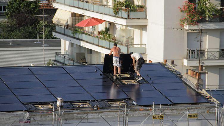 Des ouvriers posent des panneaux solaires sur le toit d'un immeuble ancien. Illustration (BRUNO LEVESQUE / MAXPPP)