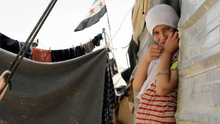 Jeune Syrienne devant sa maison, dans le camp de Zaatari, le 18 mai 2013. Avec ses 160.000 réfugiés, ce camp est devenu la 5e ville de Jordanie. (AFP PHOTO / KHALIL MAZRAAWI)