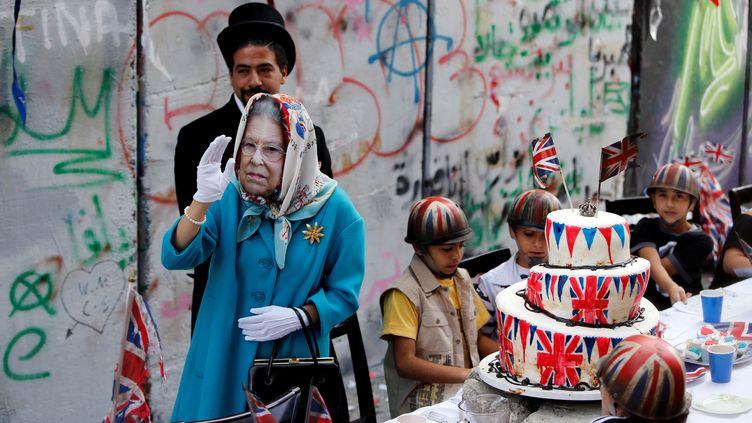 """Une personne déguisée en la reine Elizabeth II participe à la """"cérémonie d'excuses"""" organisée par l'artiste britannique Bansky, en Cisjordanie, le 1er novembre 2017. (MUSSA QAWASMA / REUTERS)"""