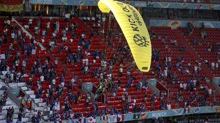 Un militant de Greenpeace manque de s'écraser dans une tribune de l'Allianz Arena, à Munich, avant la rencontre entre la France et l'Allemagne, durant l'Euro de football, le 15 juin 2021.   (ALEXANDER HASSENSTEIN / AP / SIPA)