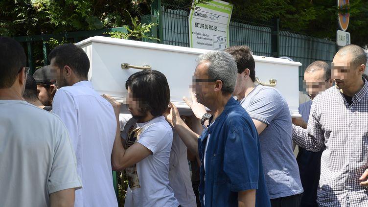 Près de Paris, à Orly, le 16 juillet 2014,des personnes portent le cercueil de l'enfant mort en colonie de vacances en Ariès. (BERTRAND GUAY / AFP)
