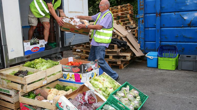 Des bénévoles des Restos du cœur récupèrent un don de nourriture d'une grande surface à Annecy, le 9 juin 2015. (MAXPPP)