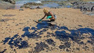 Une volontaire nettoie la plage de Lauro de Freitas, dans l'état de Bahia, au Brésil, le 3 novembre 2019. (ANTONELLO VENERI / AFP)