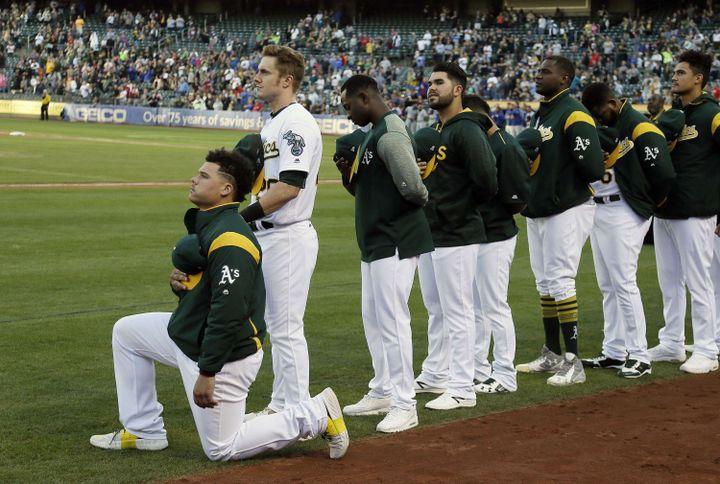 Le joueur de baseball Bruce Maxwell, des Oakland Athletics, s'agenouille pendant l'hymne américain, avant un match, le 23 septembre 2017. (ERIC RISBERG / AP / SIPA)
