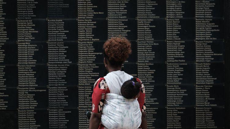 Une femme et son bébé devant le murportant des noms de victimes du génocide du Rwanda, au mémorial de Kigali. (YASUYOSHI CHIBA / AFP)