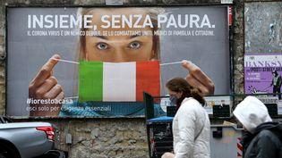 Des personnes marchent dans la rue devant une affiche incitant à se protéger avec un masque pour lutter contre le coronavirus, le 22 mars 2020, àNaples. (CARLO HERMANN / AFP)
