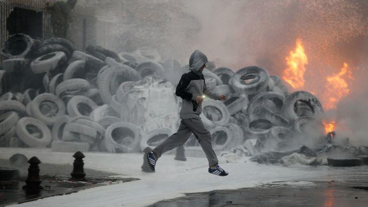 Un homme court devant un tas de pneus enflammés par des agriculteurs en colère devant la préfecture de la Manche, à Saint-Lô, mercredi 19 août 2015. (CHARLY TRIBALLEAU / AFP)