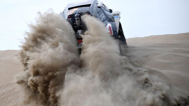 La voiture pilotée par Oscar Fuertes avec Diego Vallejo comme co-pilote franchit une dune vers la ville de Pisco (Perou), dans l'étape du 7 janvier 2018. (FRANCK FIFE / AFP)