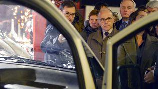 Bernard Cazeneuve,ministre de l'Intérieur, face au véhicule du forcené qui a renversé 10 personnes sur le marché de Noël à Nantes (Loire-Atlantique), le 22 décembre 2014. ( BENOIT TESSIER / REUTERS )