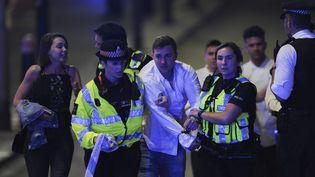 Des policiers escortent un passant, alors qu'ils sécurisent la scène de l'attaque terroriste qui a frappé Londres (Royaume-Uni), le 3 juin 2017. (DANIEL SORABJI / AFP)