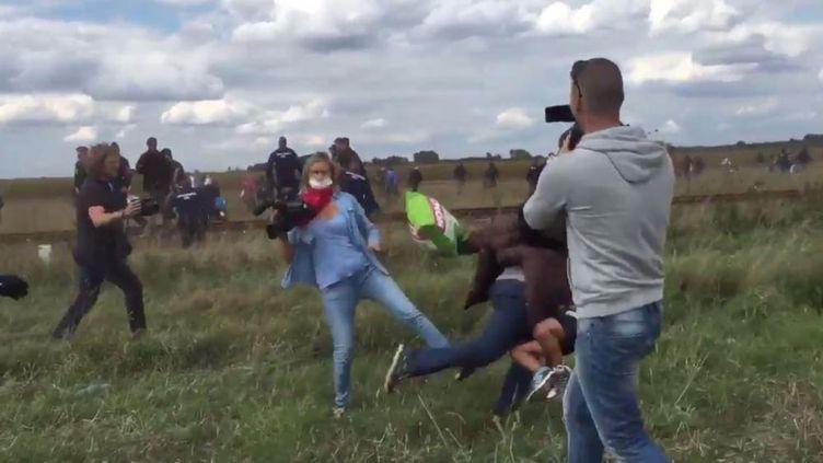 Une journaliste de la chaîne hongroise N1TV fait un croche-pied à un migrant près de la frontière serbe, mardi 8 septembre 2015. (STEPHAN RICHTER / TWITTER)