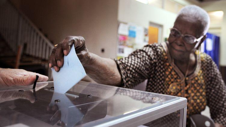 Un électrice vote à Fort-de-France (Martinique), le 21 avril 2012, pour le premier tour de la présidentielle, avec un jour d'avance sur la métropole. (JEAN-MICHEL ANDRE / AFP)
