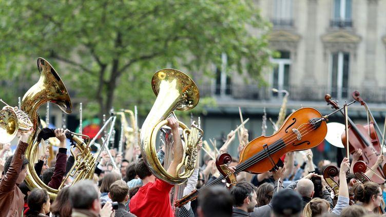 Des musiciens de l'Orchestre debout brandissent leurs instruments, le 15 mai 2016, à Paris. (KENZO TRIBOUILLARD / AFP)