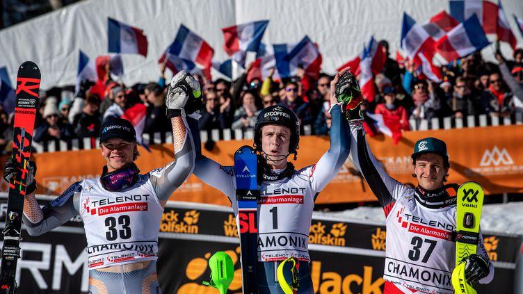 Clément Noël (au centre), entouré de Timon Haugan et Adrian Pertl fête sa victoire à Chamonix le 8 février 2020. Un an plus tard, il n'y aura pas de public pour le slalom. (JEFF PACHOUD / AFP)