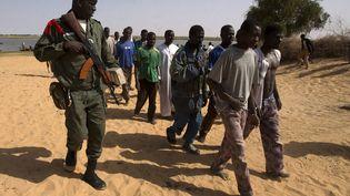 Un soldat malien escorte des prisonniers arrêtés à Kadji, dans le nord du Mali. (JOEL SAGET / AFP)