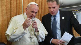 Le pape François, accompagné par le directeur du bureau de presse du Saint-Siège Greg Burke, s'exprime face auxjournalistes dans l'avion qui le ramène de Bakou (Azerbaïdjan) à Rome (Italie), dimanche 2 octobre 2016. (LUCA ZENNARO / AFP)
