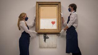 """""""L'Amour est dans la poubelle"""", une œuvre de l'artiste britannique Banksy, est présentée avant une vente aux enchères de la maison Sotheby's, le 3 septembre 2021, à Londres. (TOLGA AKMEN / AFP)"""
