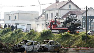 Un camion évacue les voitures brûlées, le 21 octobre 2015 à Moirans (Isère). (PHILIPPE DESMAZES / AFP)