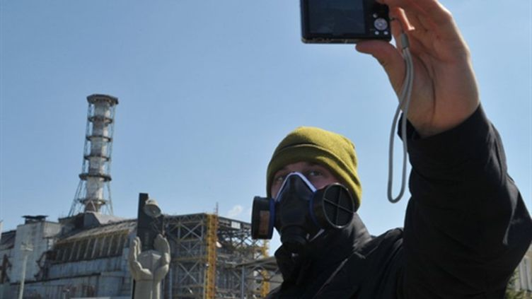 Un visiteur prend une photo, le 18/04/2011, du réacteur n°4 de Tchernobyl à l'origine de la catastrophe nucléaire. (AFP)