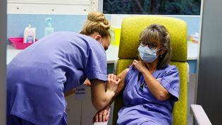 Une soignante vaccine l'une de ses collègues, le 8 février 2021au centre hospitalier de Melun (Seine-et-Marne). (THOMAS SAMSON / AFP)