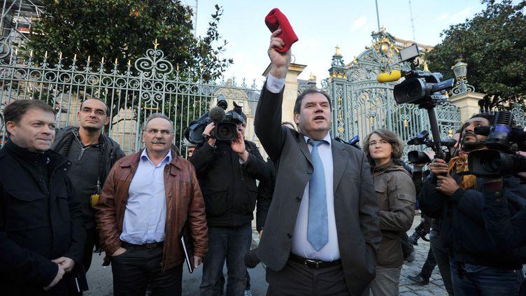 Le maire de Carhaix,Christian Troadec, brandit un bonnet rouge, symbole de la contestation en Bretagne, le 5 novembre 2013, devant la préfecture de région à Rennes (Ille-et-Vilaine). (FRANK PERRY / AFP)