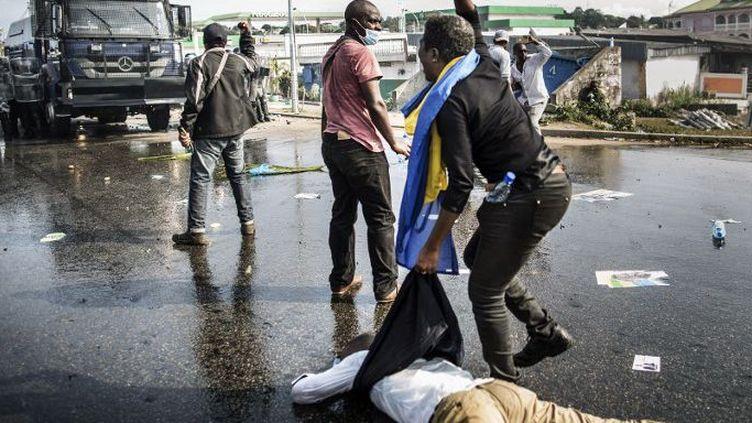 Des supporteurs de Jean Ping tentent de dégager un camarade blessé lors des affrontements avec les forces de sécurité le 31 Août 2016 à Libreville. (Photo AFP/Marco Longari)